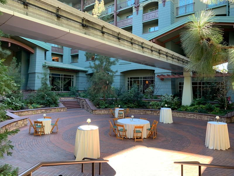 Brisa Courtyard, a circular brick courtyard decorated with round tables and white tablecloths, with monorail track overhead
