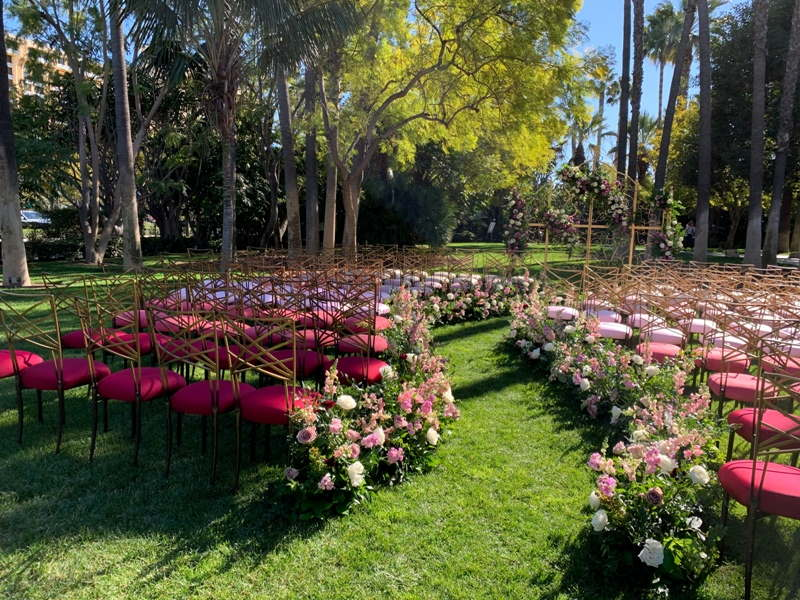 Adventure Lawn set up for a wedding ceremony, with gold and pink chairs and pink flowers lining the aisle
