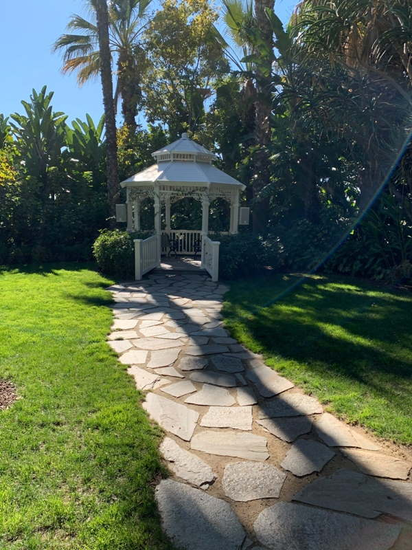 Adventure Lawn Gazebo, a small white gazebo surrounded by trees and expansive lawn
