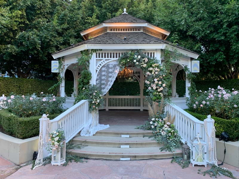 Close up of Rose Court Garden gazebo, decorated with white flowers and greenery and lace draping