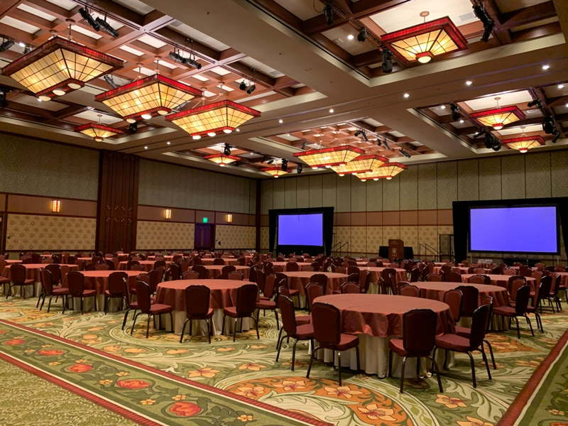 Sequoia ballroom, a large ballroom with high ceilings, set up with round tables with red chairs, and two large screens on a stage