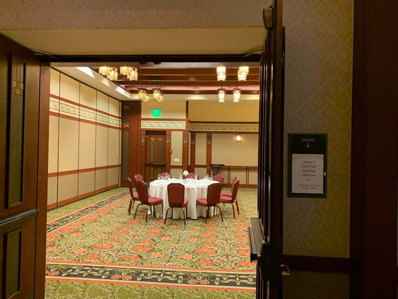 Sorrell ballroom through the main door, with round table with white tablecloth and red chairs